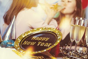 Happy New Year sign and ladies drinking