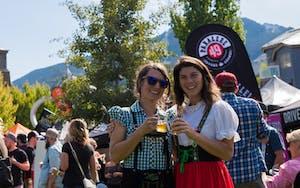 Two women in German attire, enjoying beer