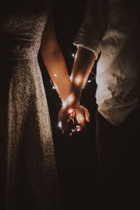 Holding hands at night, with lights