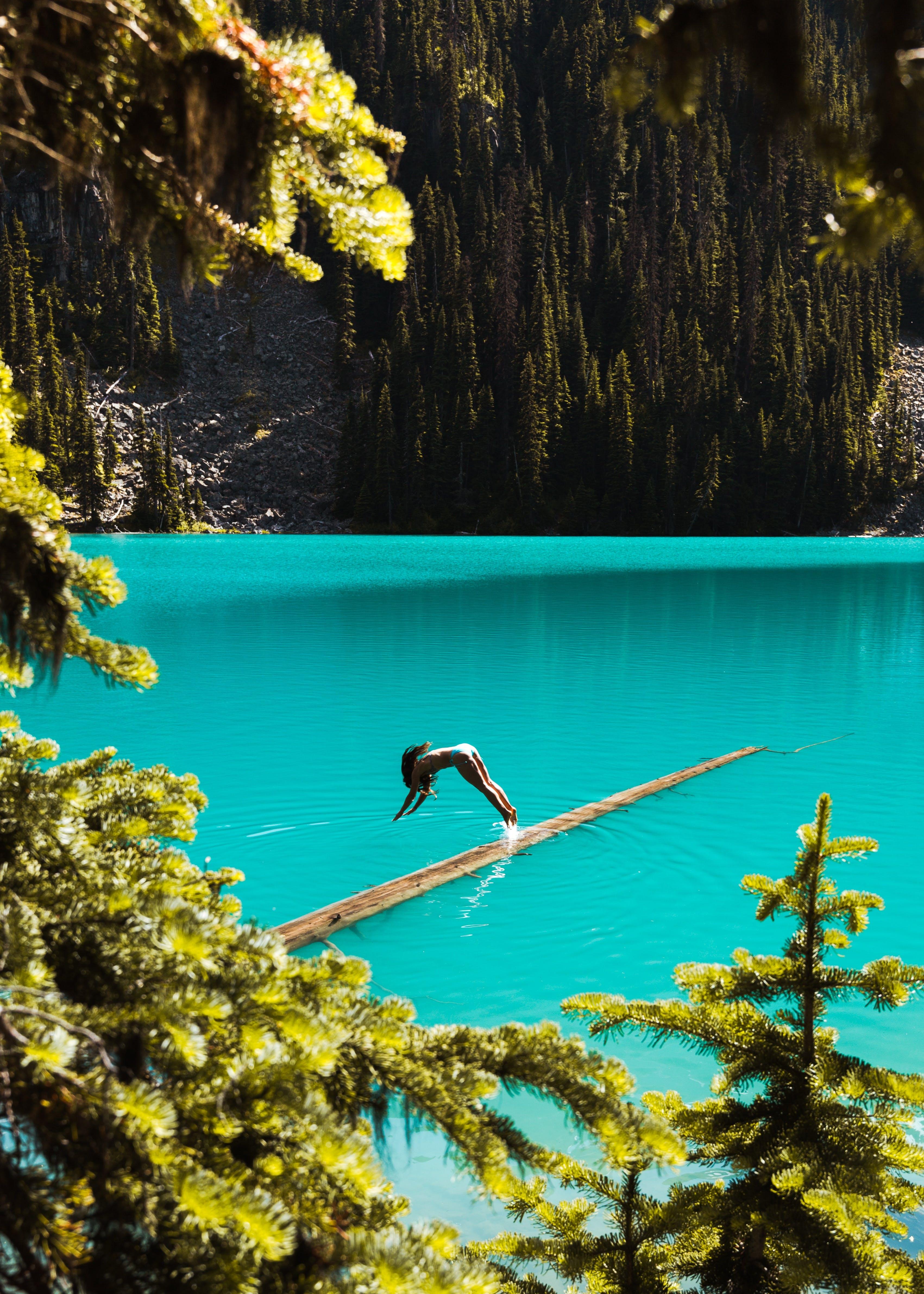Woman jumping into glacier fed lake in Pemberton