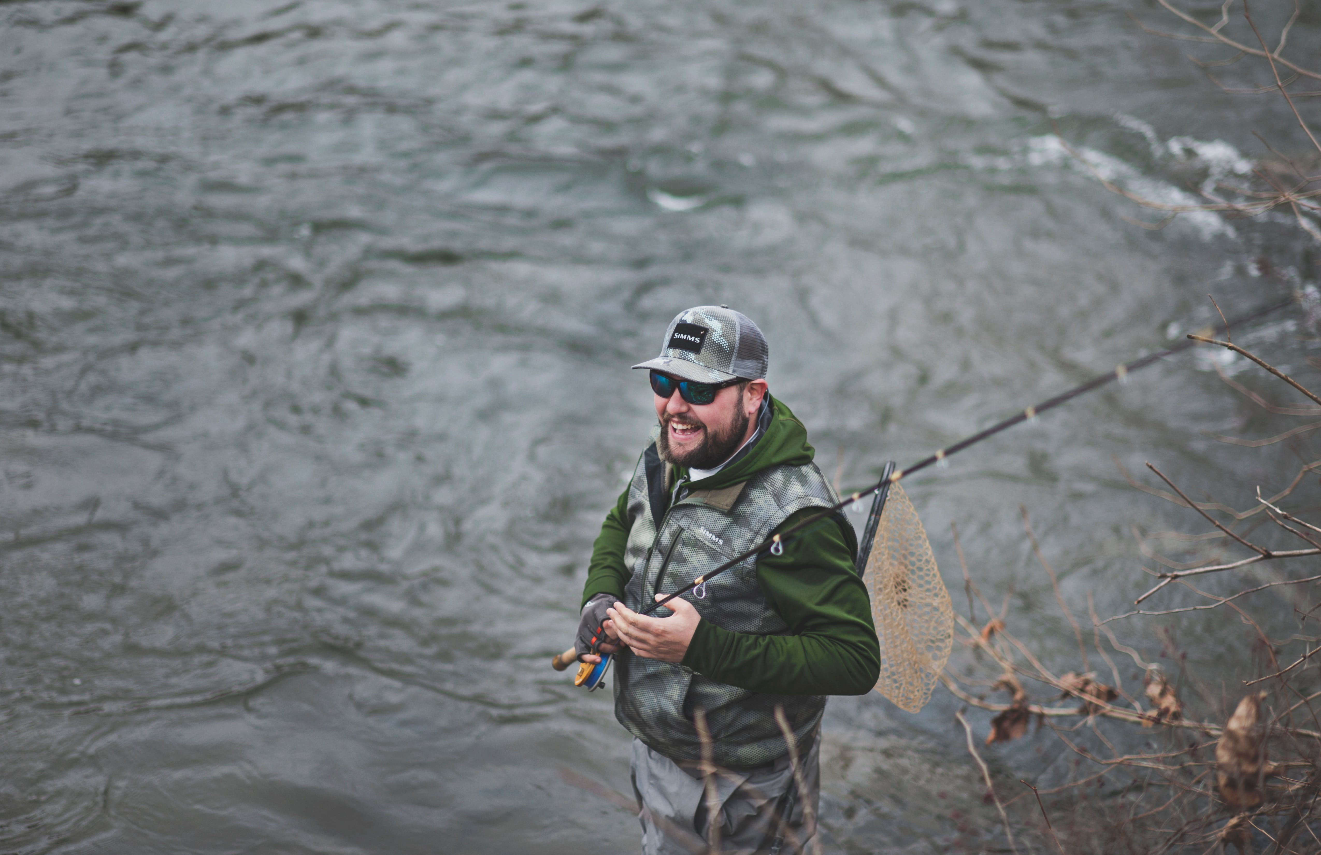Man smiling and fly fishing on a river