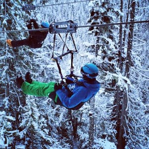 A couple zipline through the forests of Whistler