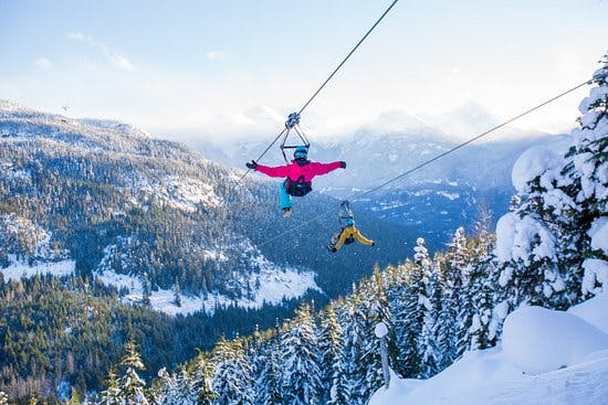 Two people zipline with Superfly in Whistler in Winter