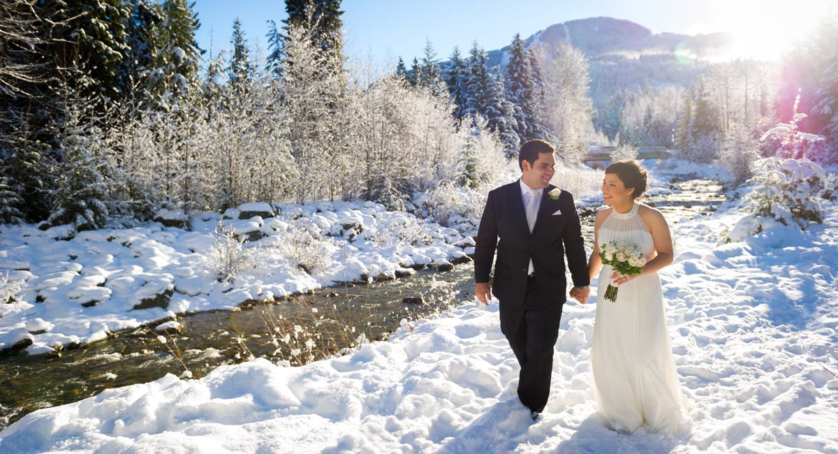 Groom and bride walking through snow, whistler