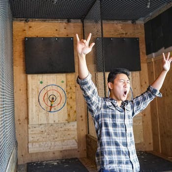 Man with arms up in celebration of axe throwing