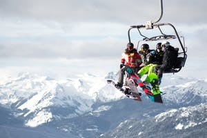 Three snowboarders sitting on a chairlift in Whistler