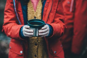 A woman in rain jacket holding a cup of hot chocolate