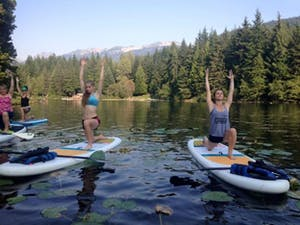 A group of women on a lake in Whistler standup paddleboard yoga.