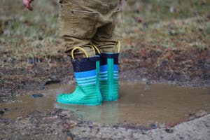 Kid with small green rubber boots playing in mud puddle.