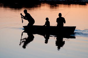 Family on a canoe at sunset in a lake.