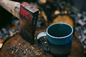 Axe stuck into a log, with a cup of coffee. Camping.