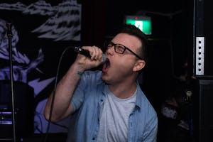 A man sings into a microphone in Karaoke