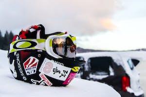 Ski helmet sitting on a car, in snow