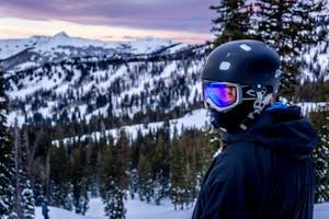 Woman wearing helmet, snowboarding