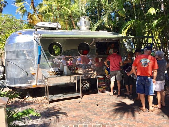 Silver airstream trailer where Garbo's Grill serves food in Key West beside Grunt's bar