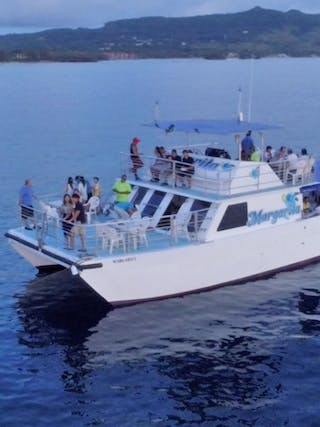 An aerial shot of the Big Sunset Cruise with people parting on the deck of the boat in Tumon, Guam