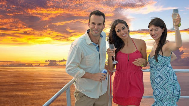 A man with a beer and two women with drink at the edge of the deck on the Big Sunset Cruise with the sunset in the background