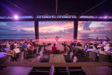 The sunset over the ocean as a performer plays the guitar at the Beach Bar & Grill in Tumon, Guam