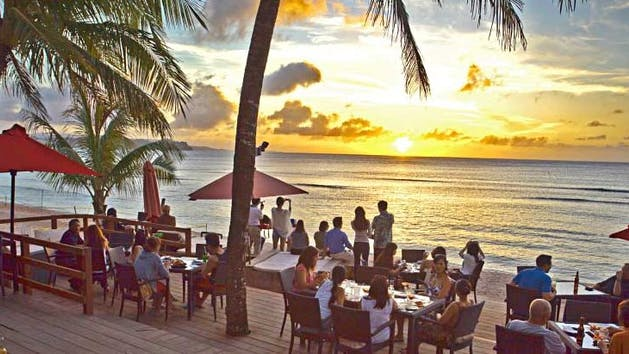 The sun setting over the ocean in Guam as onlookers enjoy a great dinner beachside at the Beach Bar & Grill in Tumon, Guam