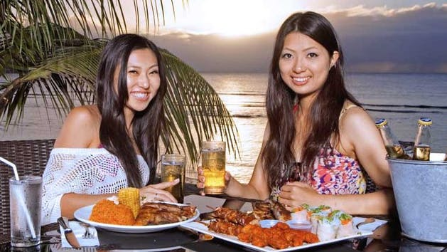 Two women enjoying BBQ and beer beachside while the sun sets over the ocean in the background in Tumon, Guam