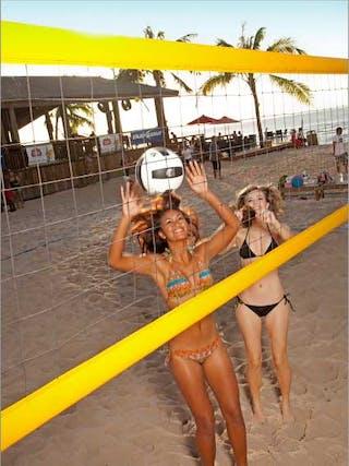 two girls in bikinis playing beach volleyball