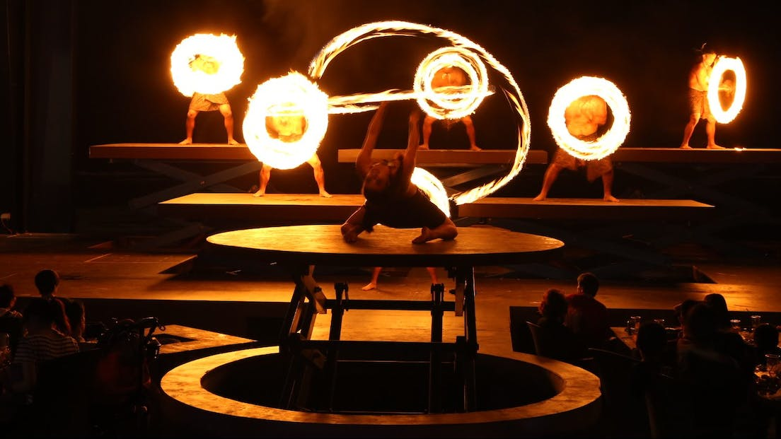 Fire dancers on platforms twirling fire at TaoTao Tasi show in Tumon, Guam