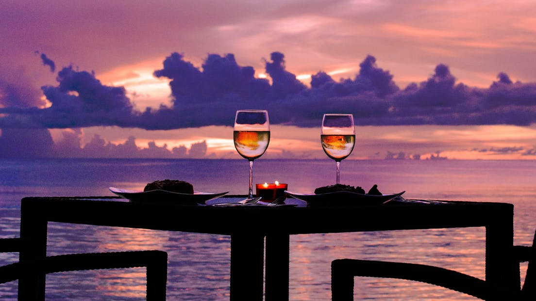 a table with two wine glasses and a candle lit as the sun sets in the distance in Tumon, Guam