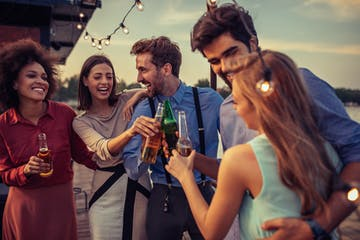Group of friends cheering with drinks on a boat cruise