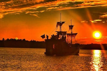 Pirate ship in the water during a sunset.