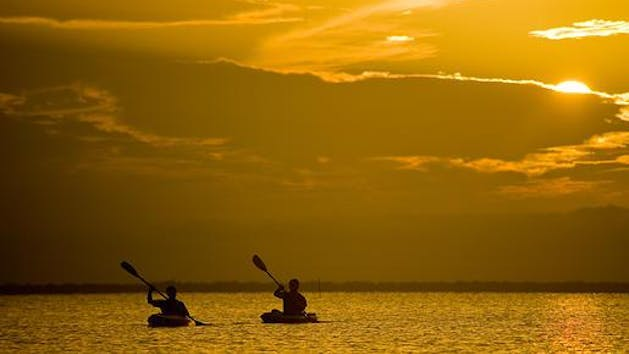 two kayakers at sunset