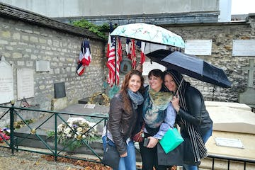 Three women posing in front of a memorial