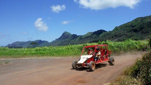 Dirt road in Kauai with ATV driving down it