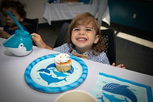 a little girl sitting at a table with a birthday cake