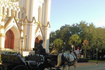 White horse pulling a black carriaged outfitted with flowers in front of a beautiful church.