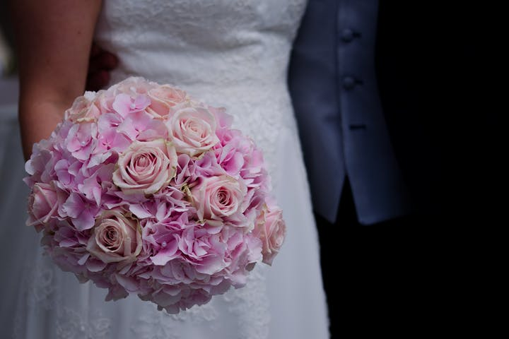 Bride a holding a big pink bouquet of flowers.