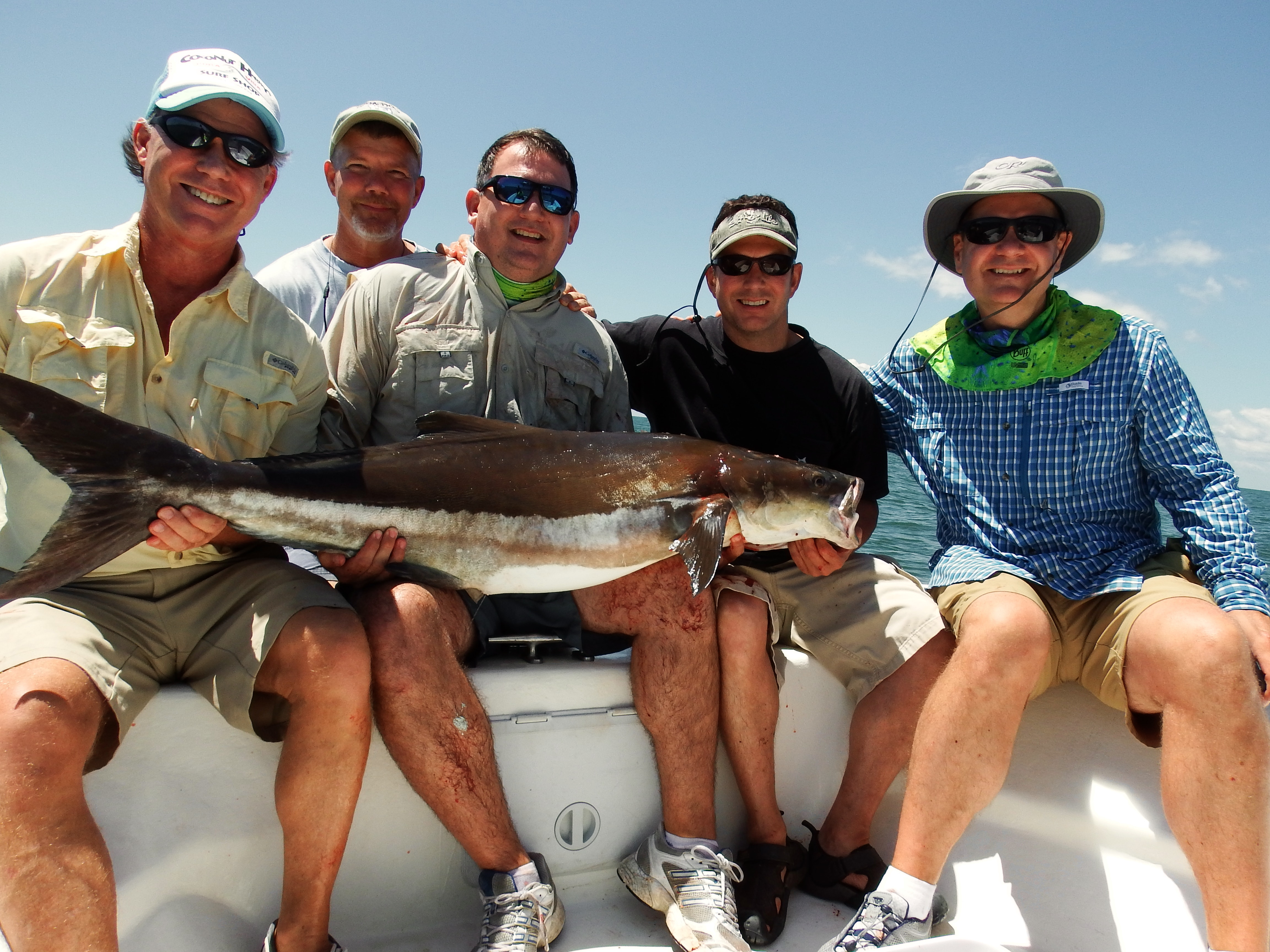 A group of fishermen smile as they hold a cobia
