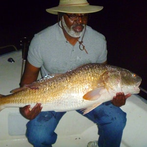 A man rests a large drum fish in his lap on a Norfolk charter