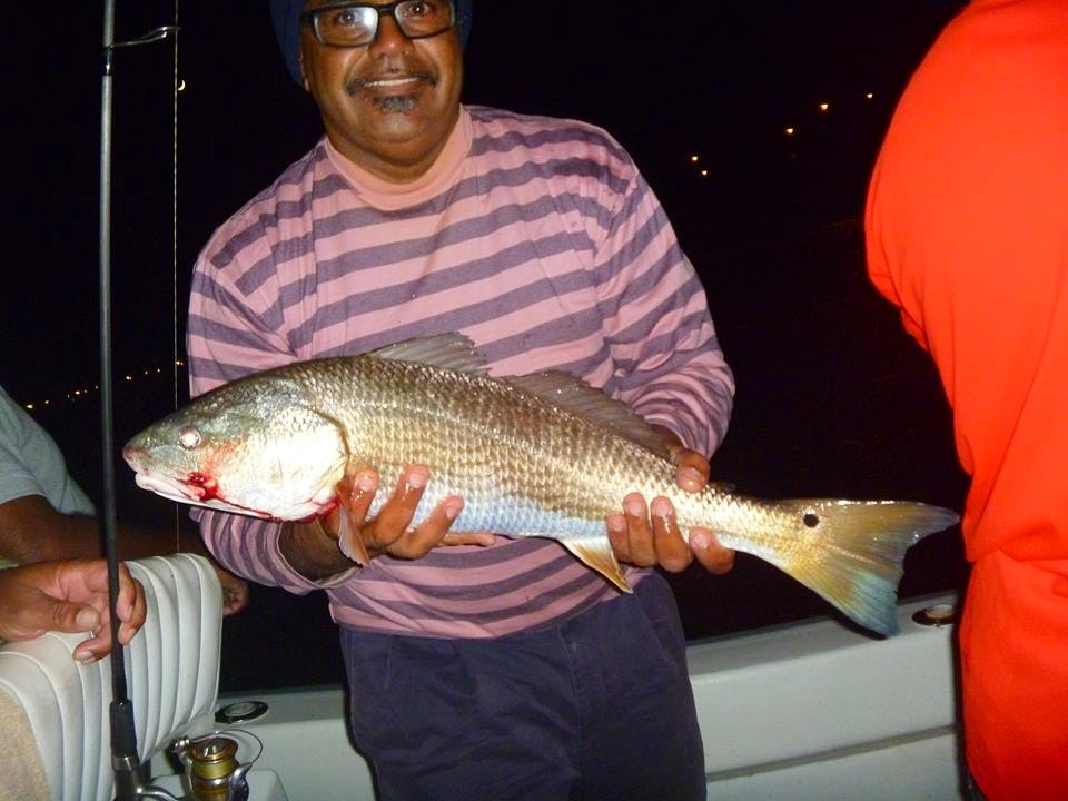 A man holds a red drum fish he caught