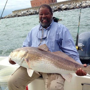 A man holds a drum fish caught on a drum fishing charter in Chesapeake Bay