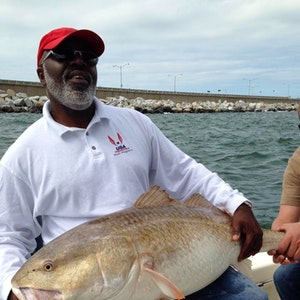 A man holds a drum fish he caught by the pier in Chesapeake Bay