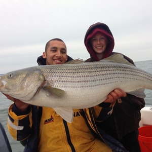 A huge striped bass caught on a cloudy day