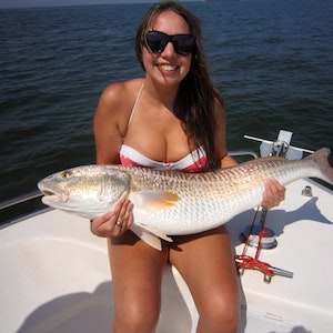A woman holds a red drum she caught while fishing