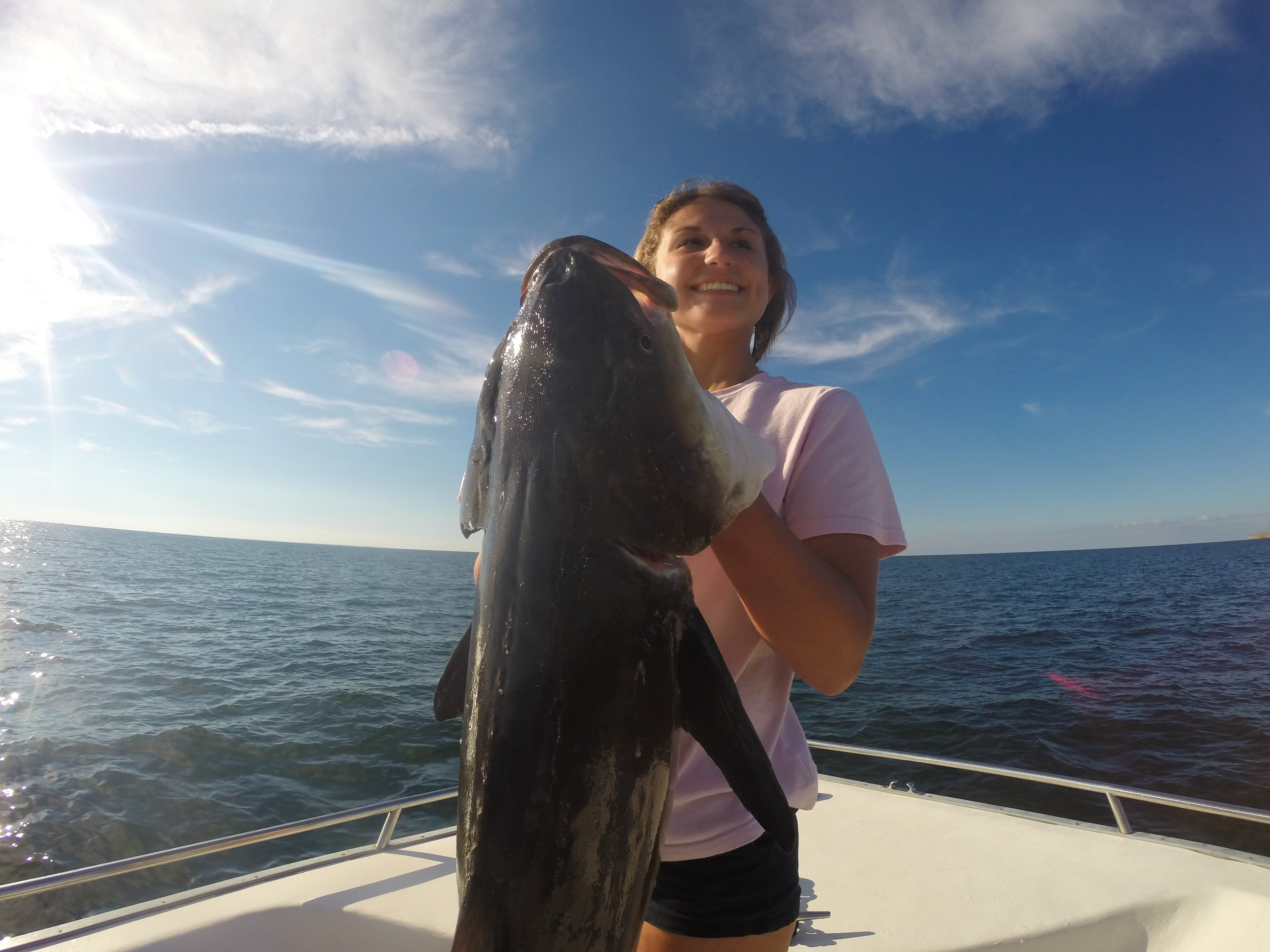A woman smiles as she holds up a massive cobia
