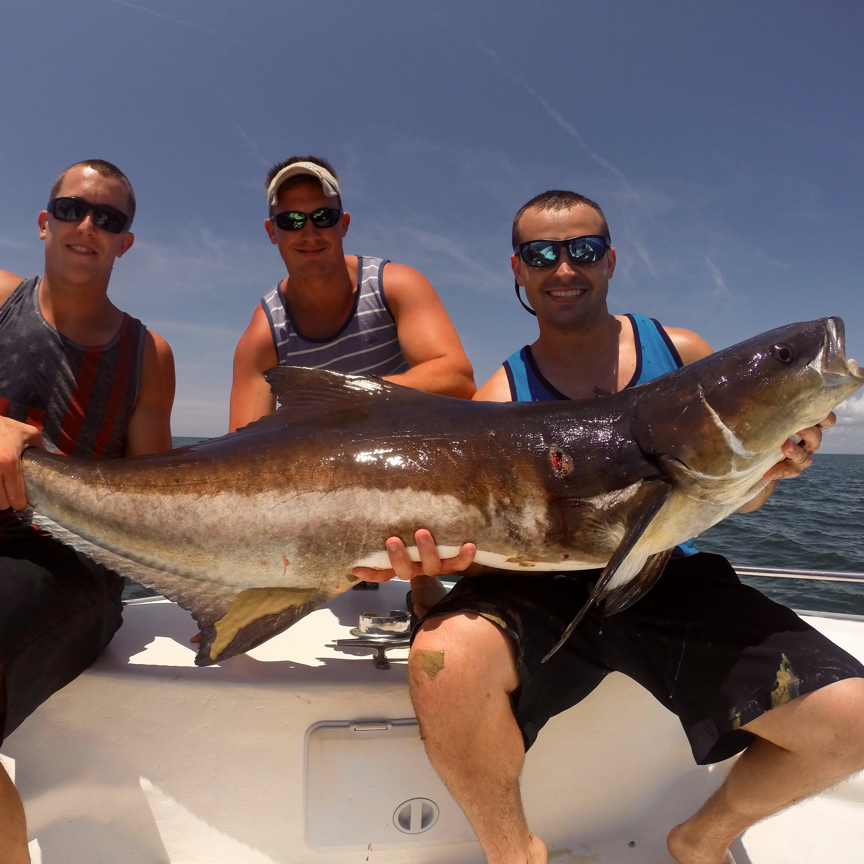 A group smiles after they catch a fish on a cobia fishing charter