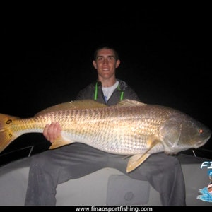 A young man smiles during a red drum fishing charter