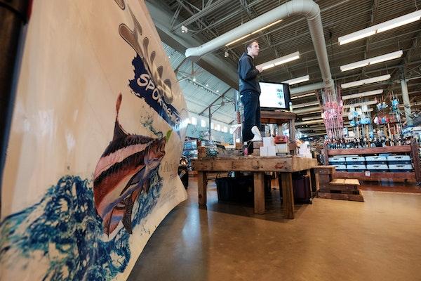 Captain Austin Hayne sets up an interactive fishing display at a fishing store
