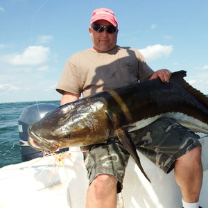 A man shows off the cobia he caught