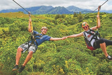 2 people holding hands while ziplining side by side