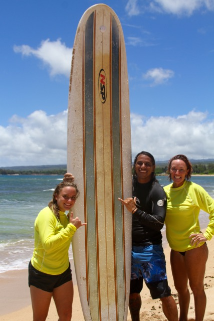 Locals standing by a surf board.