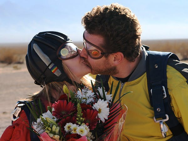 A couple kissing after completing a skydive wedding